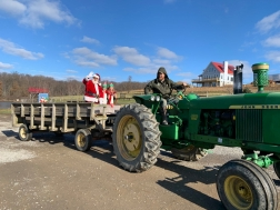 Santa and his elves in the bed of a tractor going on a hay ride.