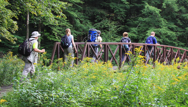 A group of hikers cross a bridge on the North Country Trail.