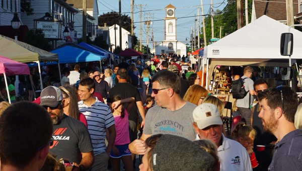 Many people enjoy an outdoor summer festival on the street.