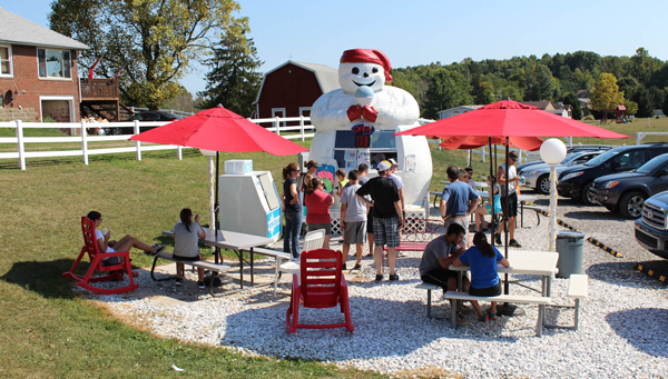 People line up in front of a frozen treat stand that is a large snowman eating a snow cone.