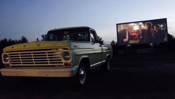 A pickup truck is backed up in front of an outdoor movie screen at the Starlight Drive-In Theater.